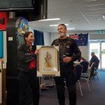 Minxy handing over Butch's painting after the winning bid